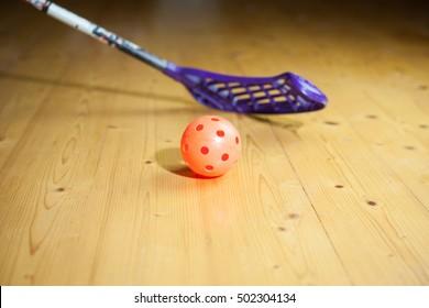 An orange ball and hockey on the floor; close-up (focus on ball;