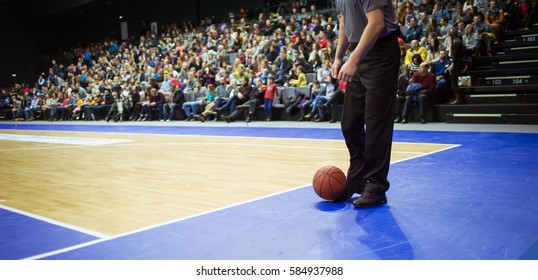 The orange ball is on the basketball court next to the referee. In the background sitting in the stands fans. In a basketball game break