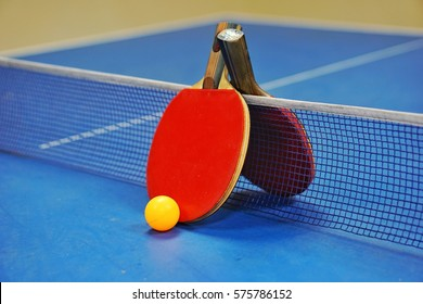 Orange ball with a table tennis racket red and black on a blue table with blurred background, indoor games