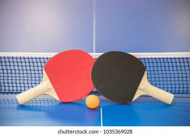 Orange ball for table tennis and two wooden rackets of red and black color on a blue table with a grid