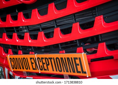 "Orange banner in the front of the truck with french text ""Convoi Exceptionnel"", translation: ""Exceptional Convoy"". Oversize load international symbol"