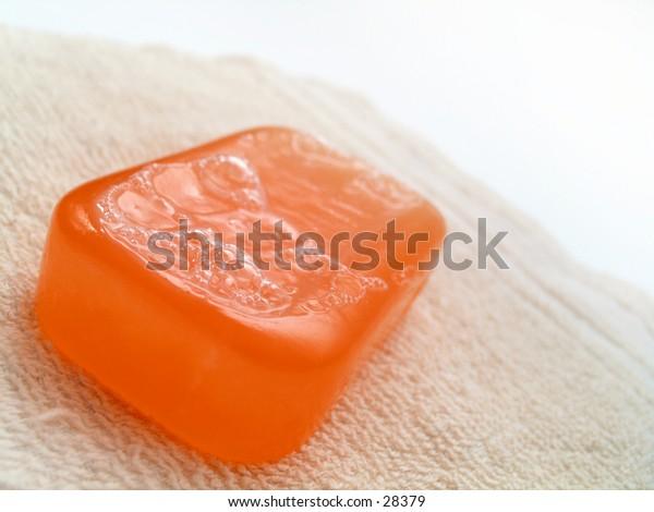 Orange bar of semi-transparent soap on a beige/tan colored dry washcloth.