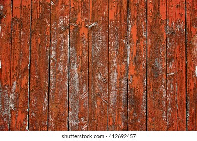 Orange barn wall with textured peeling paint off the side of the wooden boards