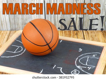 An orange basketball on a wood floor in front of a wood wall with set plans is a great image for basketball season, March Madness,or championship playoffs. Set plans are  on blackboard. Text added.