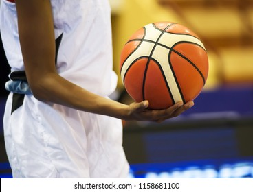 The orange basketball is in the basketball player's hand