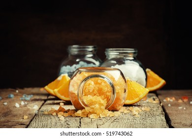Orange bath salts in a glass jar on a vintage wooden background, selective focus