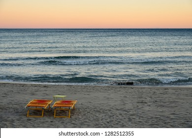 Orange beach beds and table on a empty sandy beach near the water's edge at sunset, Alassio, Liguria, Italy
