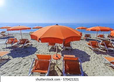 Orange beach umbrellas and couches on blue sky and sea background on the beach of Italy. Popular Tourist Resort at Adriatic Sea.