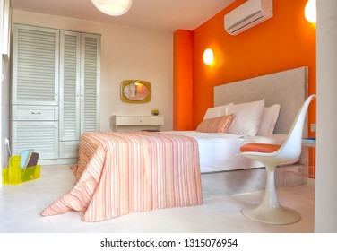 Orange and Beige colored master bedroom with cupboard, pillows, air conditioner, mirror, chair and lamps.
