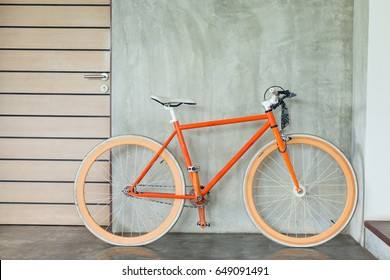 orange bicycle parked decorate interior living room modern style with cement mortar wall background