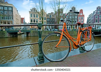Orange bike along the canals in Amsterdam the Netherlands