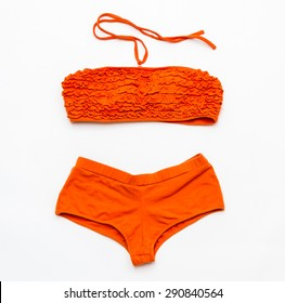 Orange bikini swimsuit on white background for design.