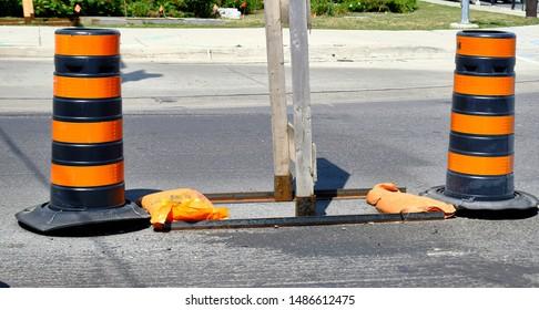 Orange and black road  construction cones on pavement