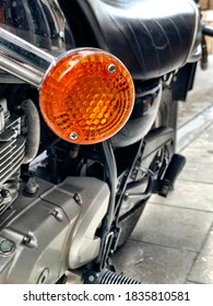 Orange blinker light on a black vintage motorcycle