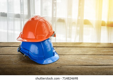 orange, blue hard safety helmet construction hat for safety project of workman as engineer or worker, Engineering Construction worker equipment, on wooden floor, window light and curtain is background