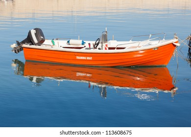Orange boat moored in the harbor. Blue water. Diving flag. Inscription training boat. Reflected in the water.