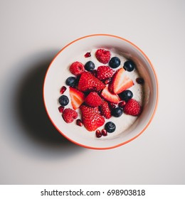 Orange bowl porridge with red and blue berries top down view