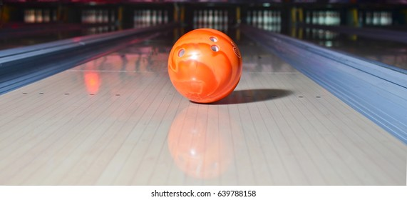 Orange bowling ball on the track. Active leisure. Sport game.