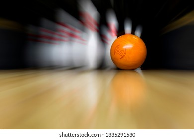 An orange bowling ball is rolling at great speed into white skittles. Copy space wooden bowling alley