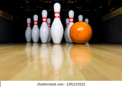 orange bowling ball and white skittles stand on a wooden bowling alley. copy space