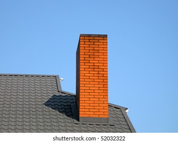 orange brick pipe and black roof on blue sky in sunny day, modern construction, environment diversity