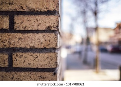 Orange brick wall close up textured on a corner street with blurred outdoor cityscape