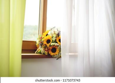 Orange bridal bouquet with sunflowers on a window shelf
