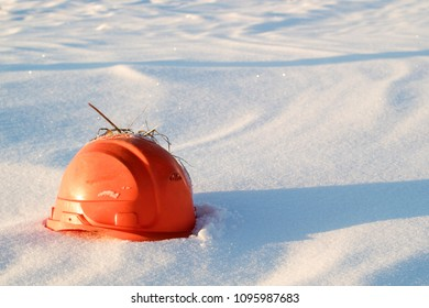 an orange broken construction helmet lying in the snow on which a snow blizzard appears