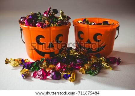 Orange buckets with colorful chocolates over white background