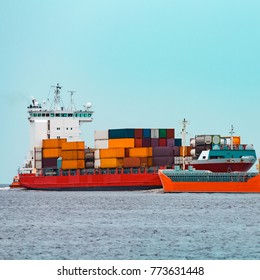 Orange bulker moving past the red container ship in Baltic sea