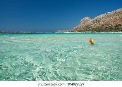 Orange buoy in the water of famous lagoun, Crete island, Greece