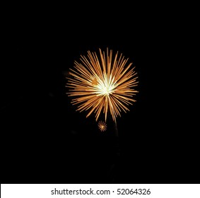 "Orange burst of fireworks with white-hot core above an orange and pink ""baby"" burst"