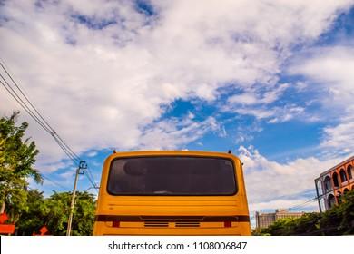 Orange bus and bright blue sky.
