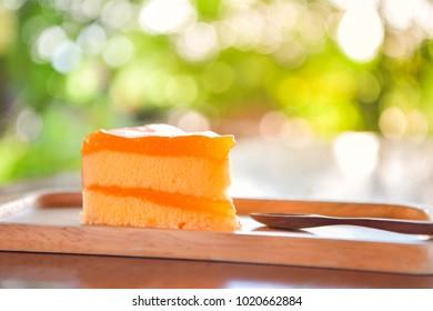 Orange cake on wooden plate, bokeh background.