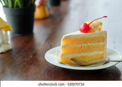 Orange Cake On Wooden Table In Coffee Shop