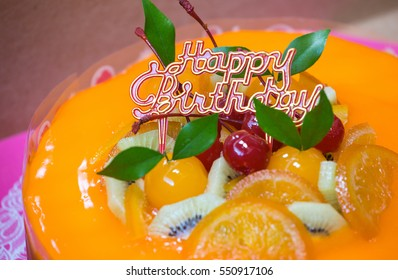 Orange cake with several fruit and label on top in the box cake