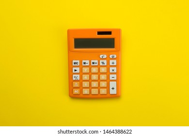 Orange calculator on a bright paper yellow background. Office supplies. Education. back to school. top view. place for text.