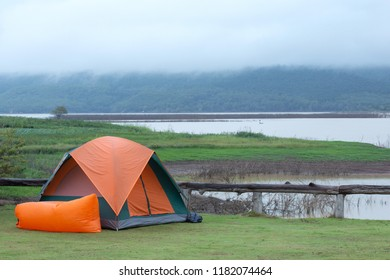 Orange camping tent over lagoon in Thailand