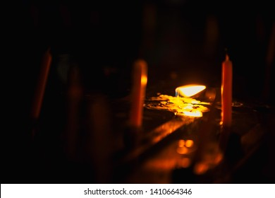 An orange candle light that resonates with water and resembles a wind that will extinguish the light.