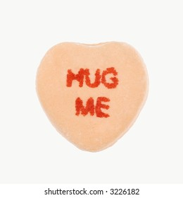Orange candy heart that reads hug me against white background.