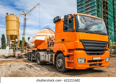 Orange car with cement on the construction site