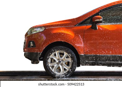 Orange car with white soap on the body in car care shop. Isolated on white background