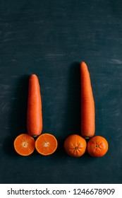 Orange and carrots on dark background, symbol of penis. Sexual maturation. sex education, man's dream. male blowjob, lgbt gay target, passion of big size, tenderness, Viagra concept, low light tone.
