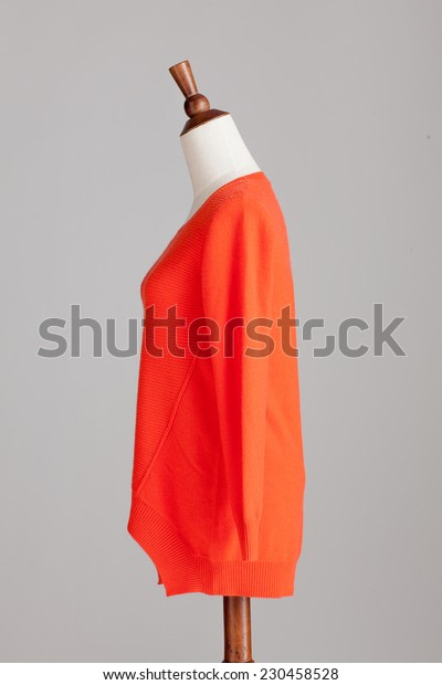 orange cashmere sweater with wood model on grey isolated