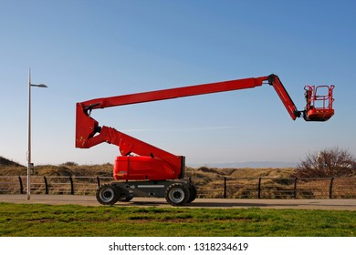 Orange cherry picker, side view against a blue sky