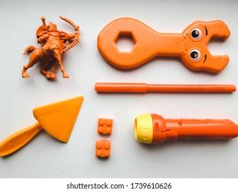 Orange children's toys on a white background: soldier, lantern, trowel, felt-tip pen, constructor parts, wrench. Dominance of orange