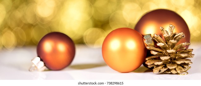 Orange christmas balls and cone in front of golden shiny background, header