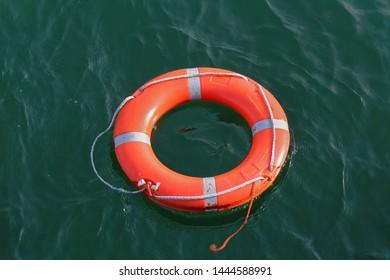 Orange circle lifebuoy floating on sea water surface
