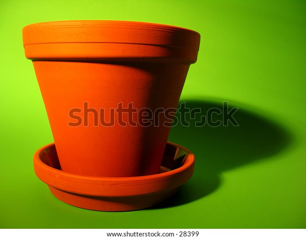 An orange clay flower pot with deep shadows on a bright green background.