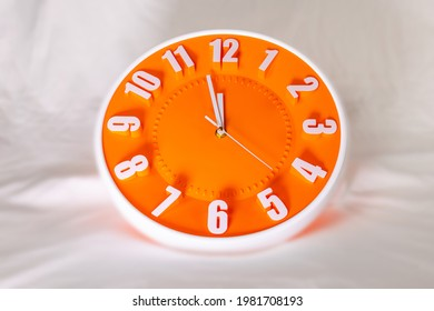 Orange clock face of a wall clock show the time. It's close to 12 o'clock. The latest report of the atomic scientist shows the doomsday clock 100 seconds to twelve.  Time is running out for mankind.